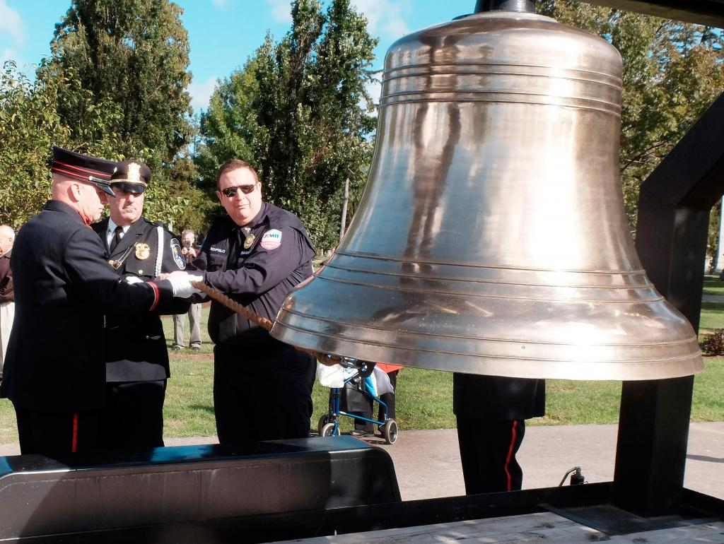 Tom Bonfiglio of American Medical Response of Rochester, David DiFante of the Rochester Police Department and Roger Rebman of the Rochester Fire Department ring the remembrance bell during a Sept. 9 ceremony dedicating the First Responders section and monument at Holy Sepulchre Cemetery in Rochester.