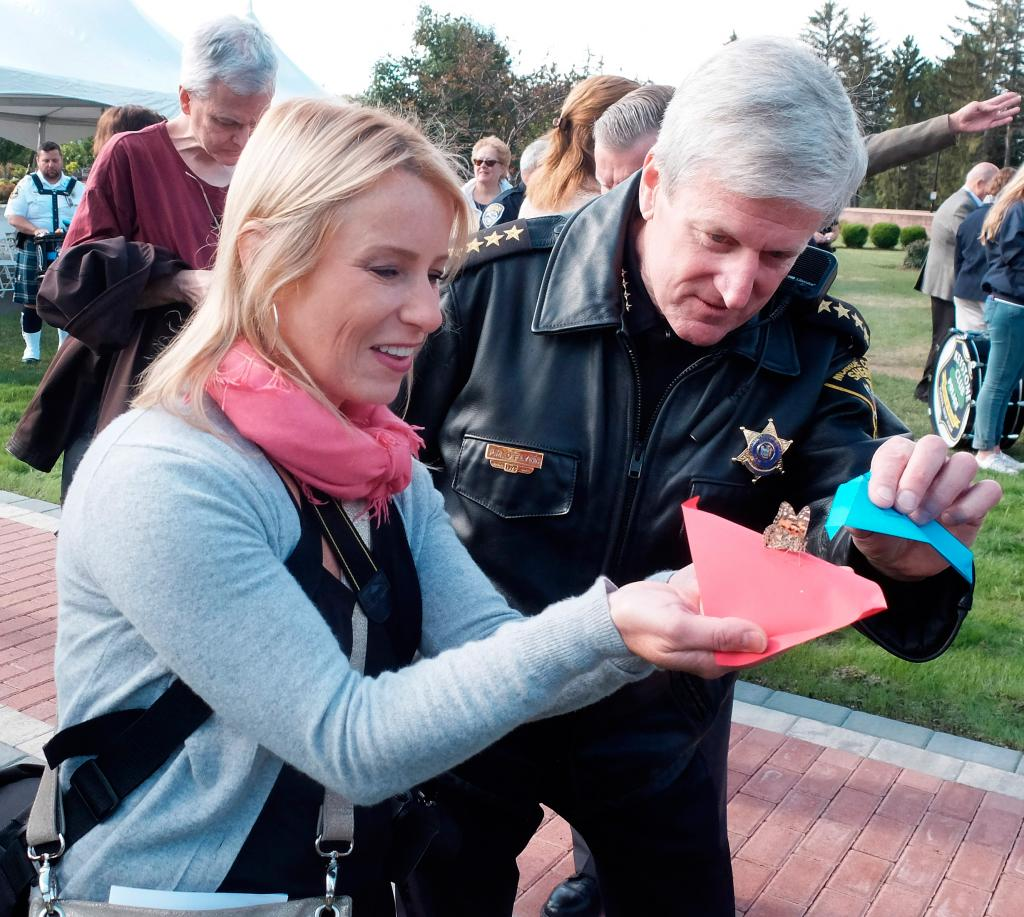 Kathryn Carangelo and Monroe County Sheriff Patrick O'Flynn release butterflies during the Sept. 9 dedication of the First Responders section and monument at Holy Sepulchre Cemetery in Rochester.