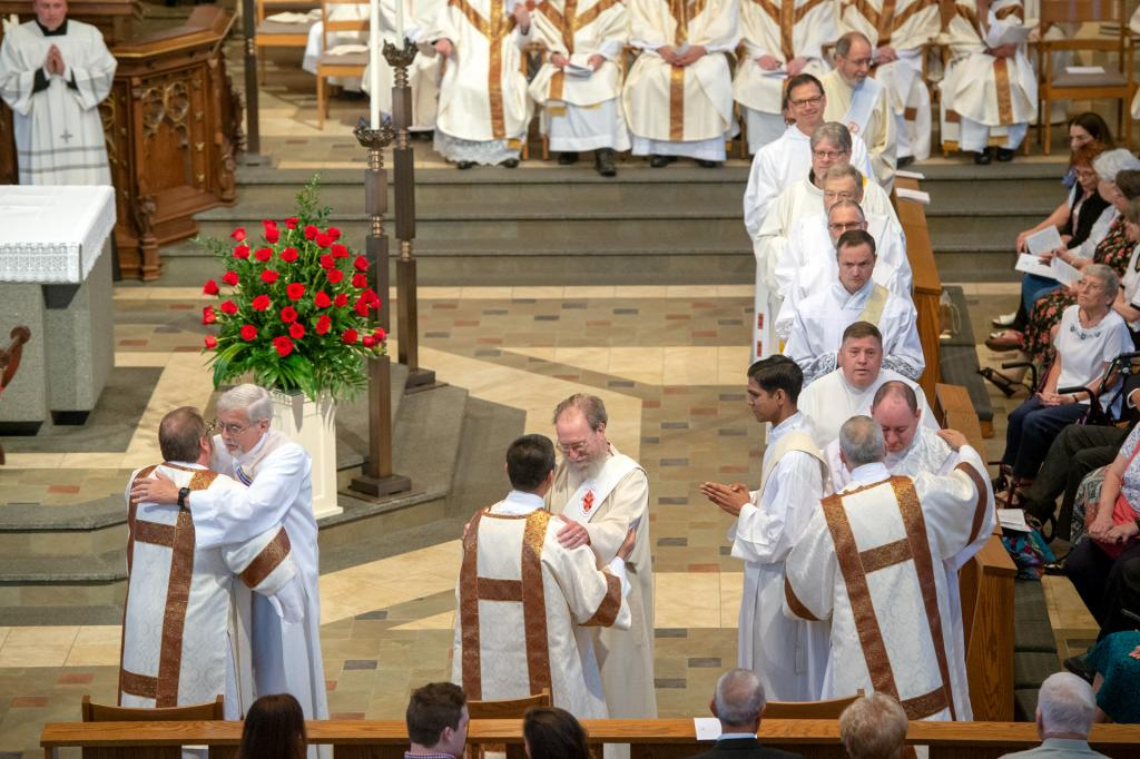 Permanent deacons line up to congratulate the newly ordained deacons.