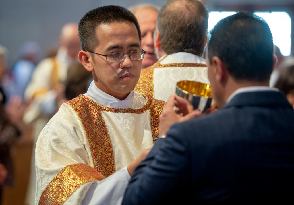 Deacon Binh-Yen Nguyen helps to distribute Communion.