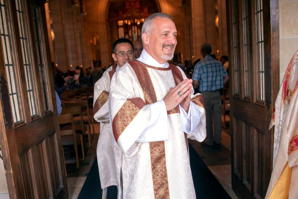 Deacon Michael Kristan recesses out of the cathedral at the end of Mass.