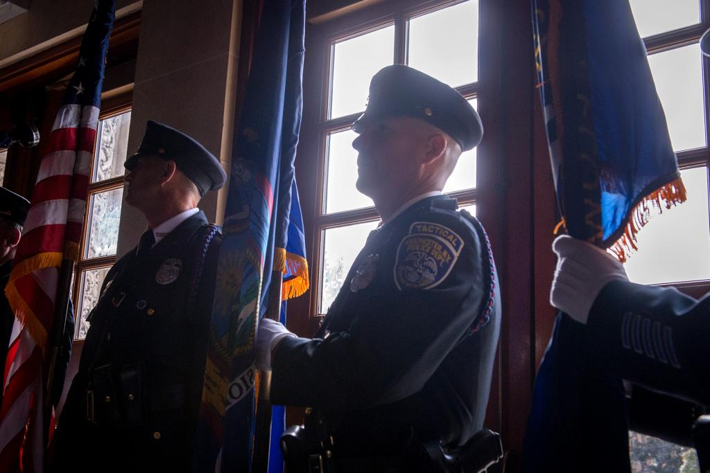 Flag-bearers with the Rochester Police Department wait to process into Mass.