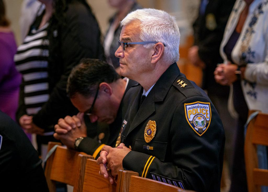 Irondequoit Chief of Police Richard V. Tantalo kneels during the Liturgy of the Eucharist.