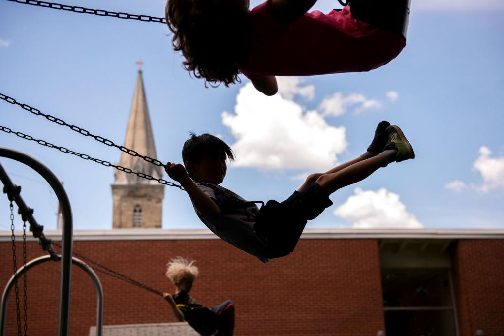 Children participating in the summer program at All Saints Academy in Corning play on the swings behind the school July 15.