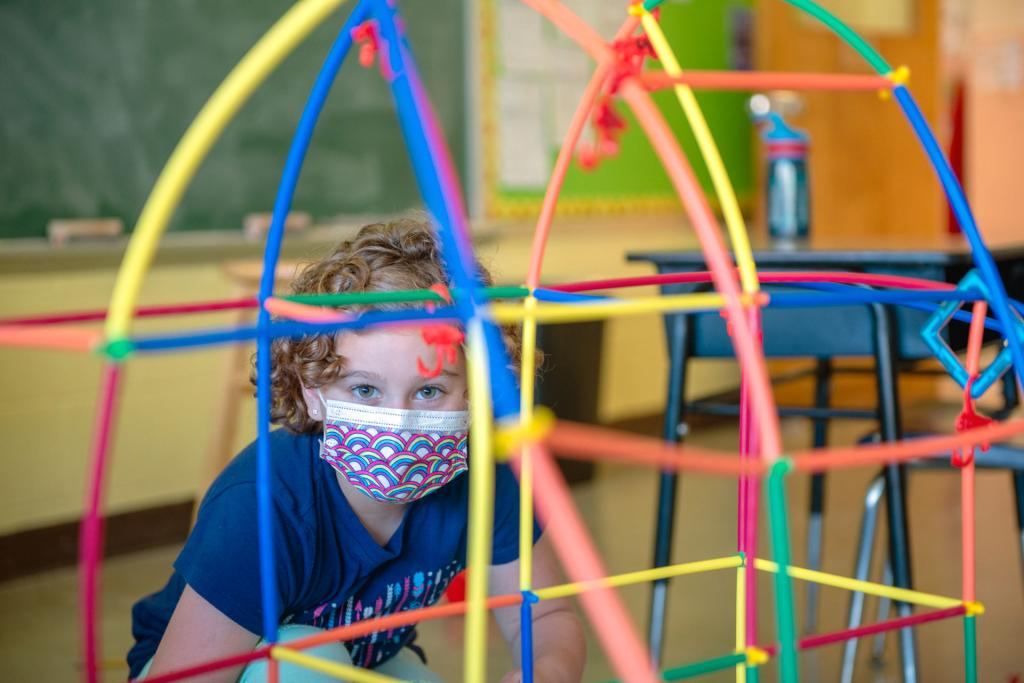 Second-grader Emily Layton wears a mask while playing in a classroom.