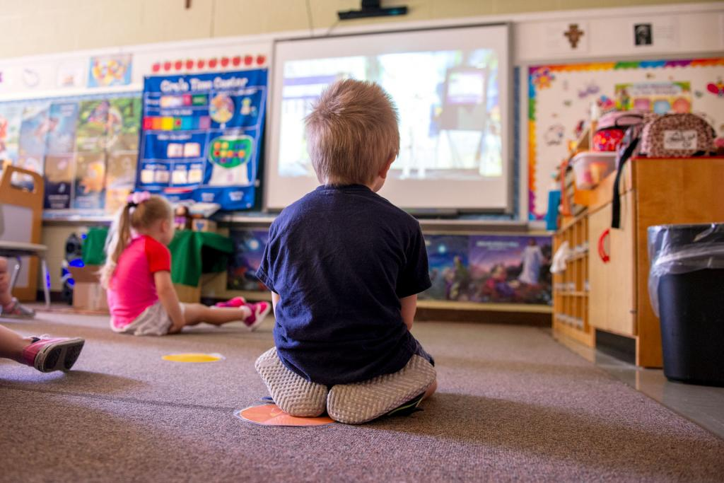 Students in the preschool classroom watch a video together.
