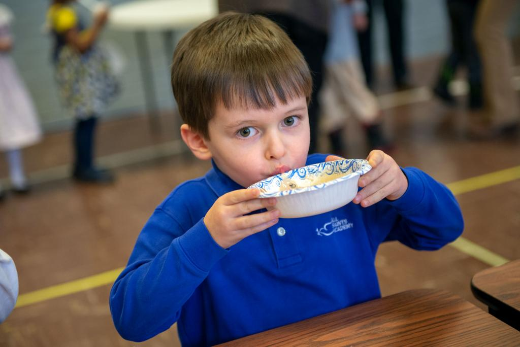 Finn Dalton sips melted ice cream from his bowl during an ice cream party Jan. 29 at All Saints Academy in Corning.