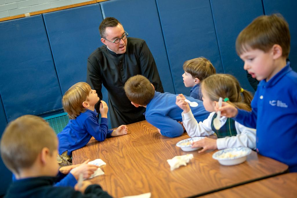 Father Mathew Jones speaks to students during the ice cream party Jan. 29 at All Saints Academy in Corning.