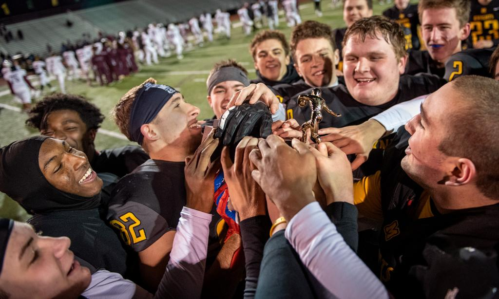 McQuaid Jesuit players reach forward to touch the Section 5 Class AA Championship trophy following their 30-27 win against Aquinas Institute Nov. 9.