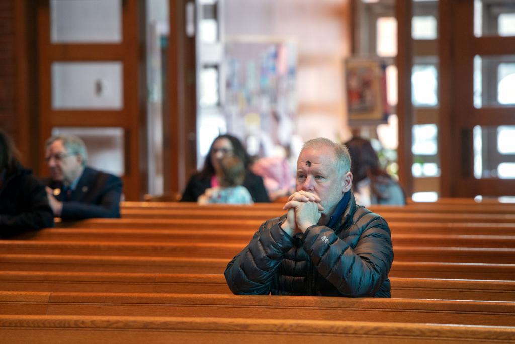 Pat Rogers kneels in prayer.