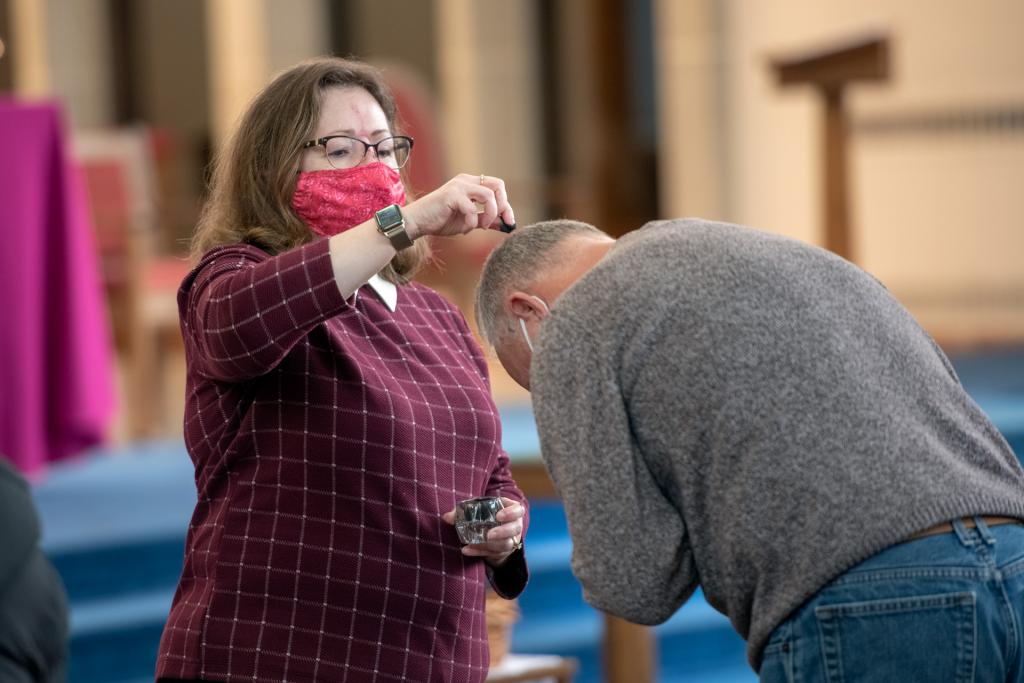 Mary Jo Trenkner sprinkles ashes on a parishioner's head at Our Mother of Sorrows.