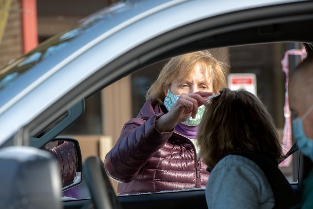 Amy Voll distributes ashes through a car window at St. John of Rochester.