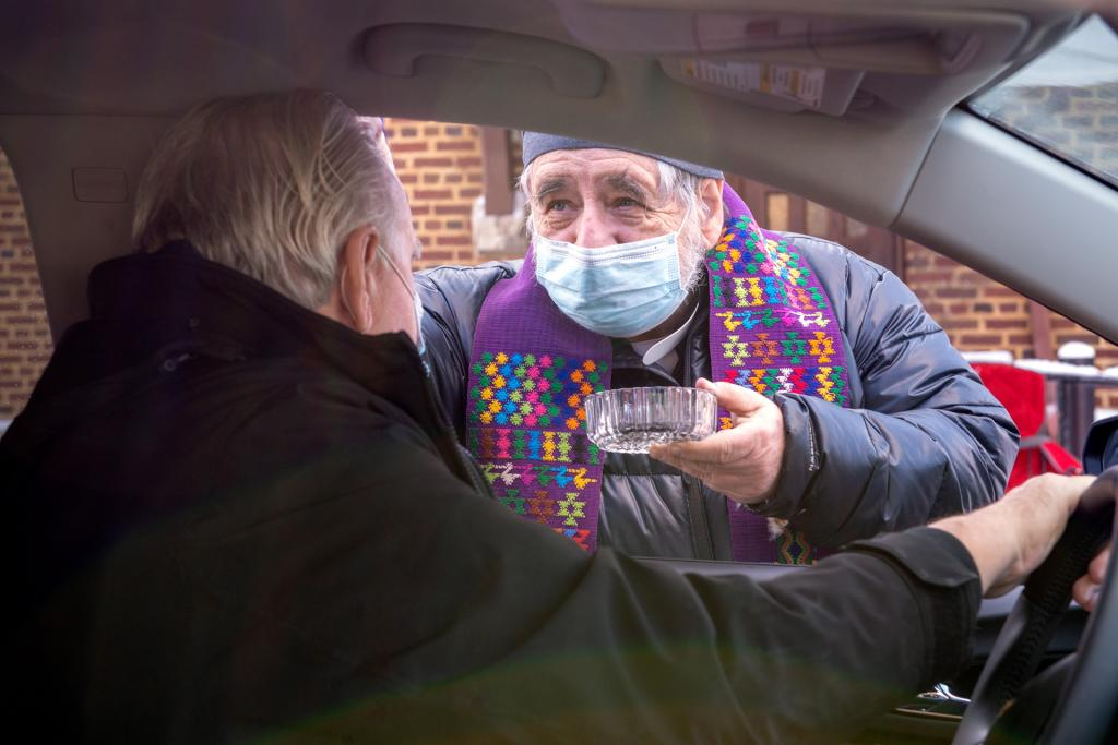 Father Raymond Fleming distributes ashes through a car window.
