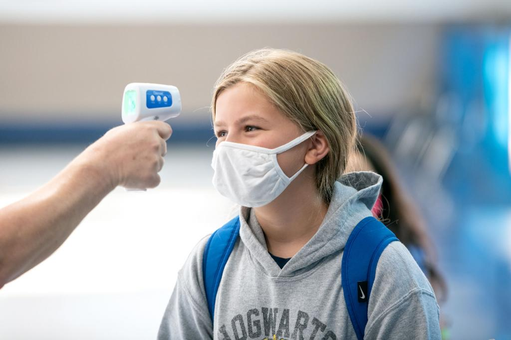 Francesca Riess has her temperature checked before heading to her classroom at Seton Catholic School.