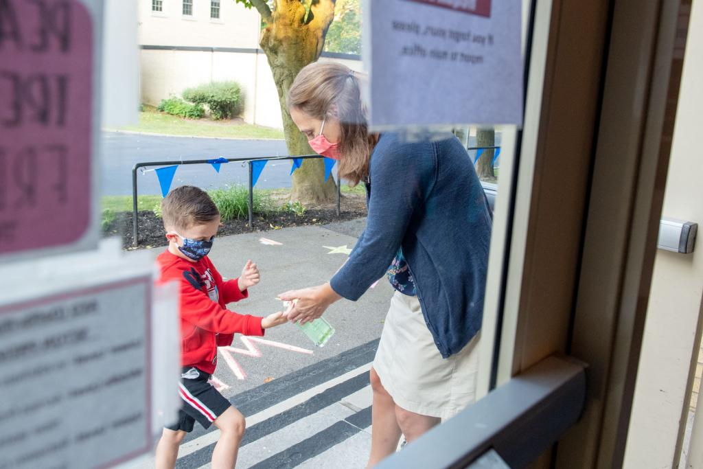 Seton Catholic School teacher Bethany Samsonik gives hand sanitizer to Anthony Morelle before he enters the school.