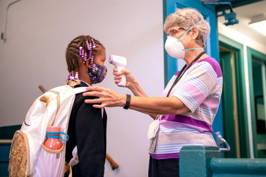 Aleeah Ross has her temperature checked by school nurse Sr. Marlene Pape before entering Nazareth Elementary School.