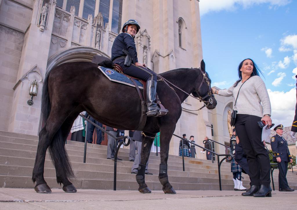 Danielle Stout pets a horse ridden by mounted officer Lisa Knapp.