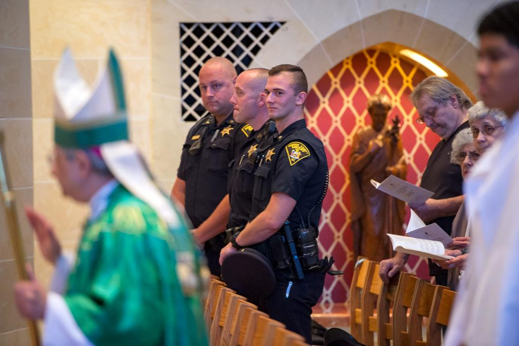 Members of the Monroe County Sheriff's Office watch Bishop Matano during the procession.