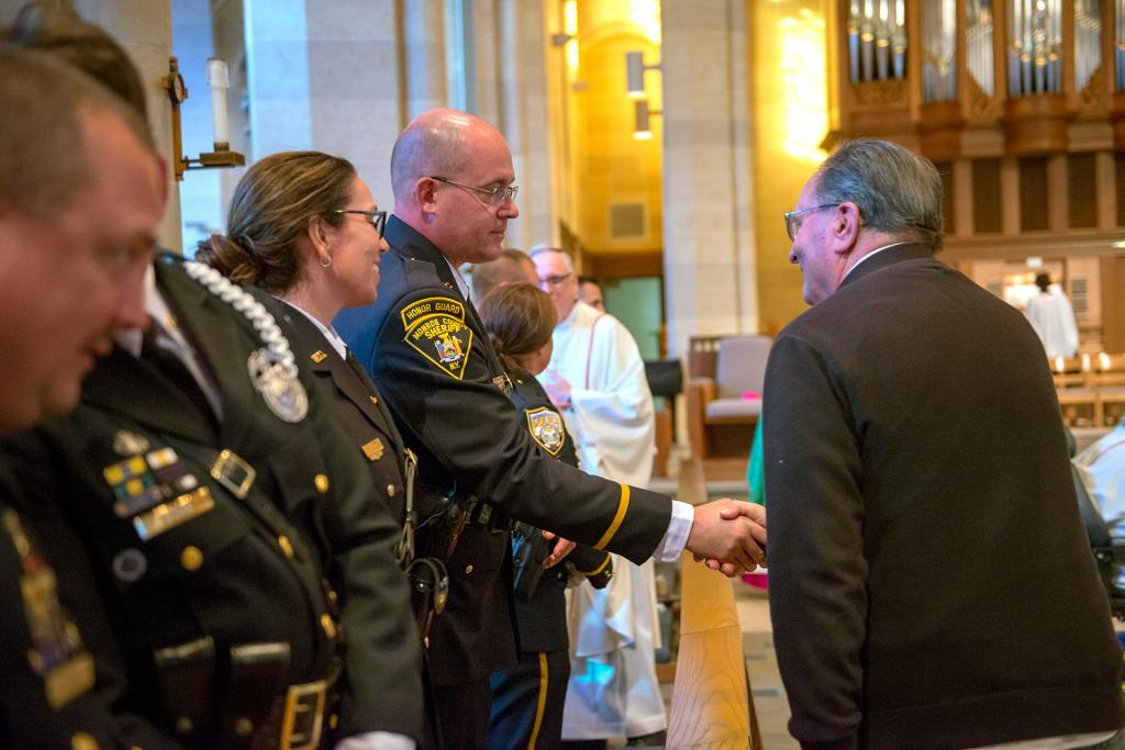 An officer and a congregant offer each other the sign of peace during Mass.