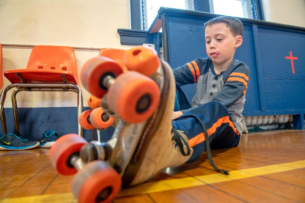 Menzo Peck straps on his roller skates before a roller-skating party at Avon's St. Agnes School Jan. 30. (Courier photo by Jeff Witherow)