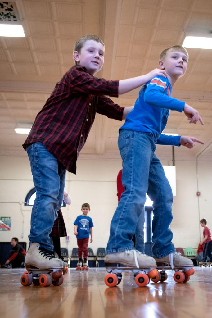 St. Agnes students hold onto one another for balance while they skate around the gymnasium Jan. 30. (Courier photo by Jeff Witherow)