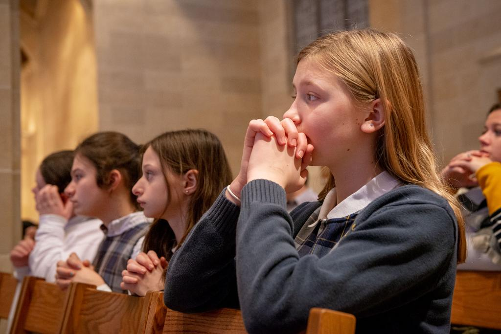Sixth-grader Lily Dale from St. Mary Our Mother in Horseheads kneels in prayer during Jan. 29 during the Catholic Schools Week Mass at Rochester's Sacred Heart Cathedral. (Courier photo by Jeff Witherow)