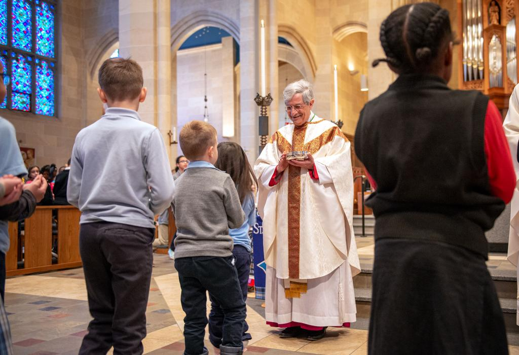 Bishop Salvatore R. Matano distributes Communion to students during the Catholic Schools Week Mass. (Courier photo by Jeff Witherow)