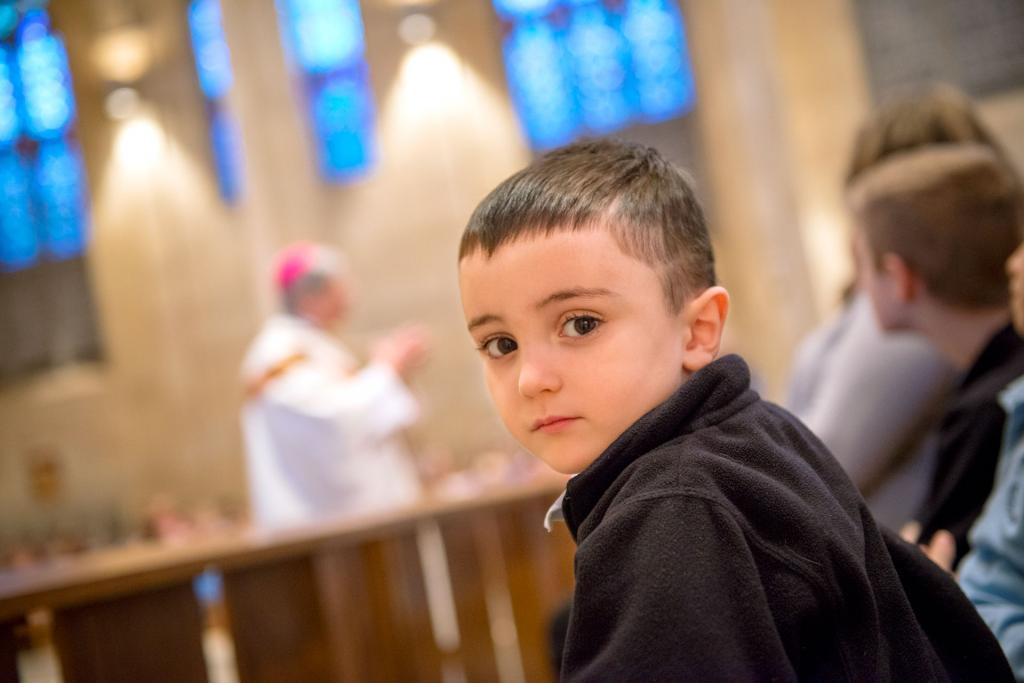 Kindergartner Nick Michael listens to Bishop Matano's homily during the Jan. 29 Catholic Schools Week Mass.
