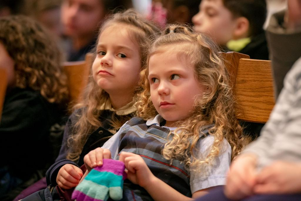 Clare Swanson (left) and Lila Merritt from Holy Cross School in Rochester sit during Mass.