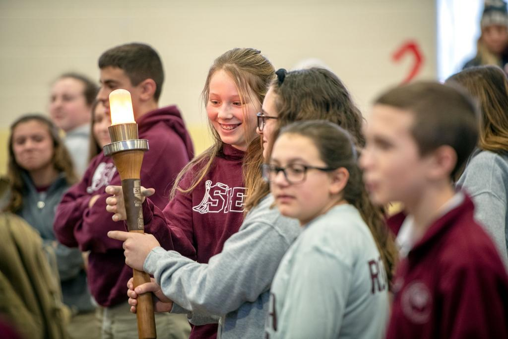 Brighton's Siena Catholic Academy seventh-grader Madeline Firpo passes the torch for the Empire State Winter Games Jan. 27. (Courier photo by Jeff Witherow)