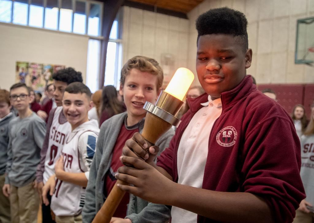Brighton's Siena Catholic Academy seventh-grader Chandler Bowman participates in the passing of the torch for the Empire State Winter Games. (Courier photo by Jeff Witherow)