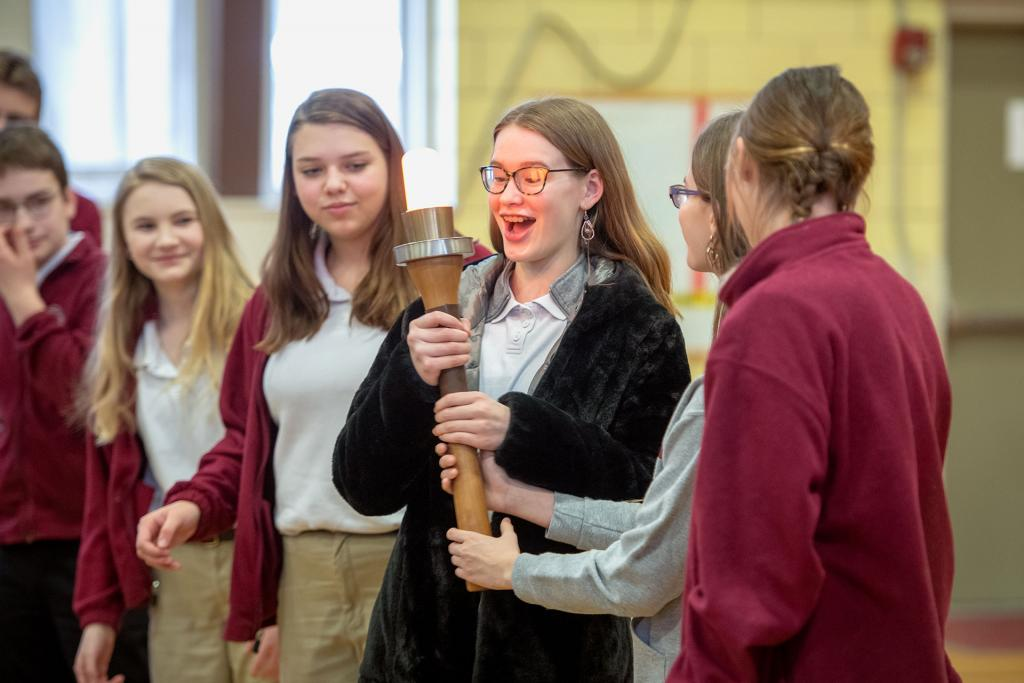 Eighth-grader Esther Davey is handed the torch for the Empire State Winter Games. (Courier photo by Jeff Witherow)
