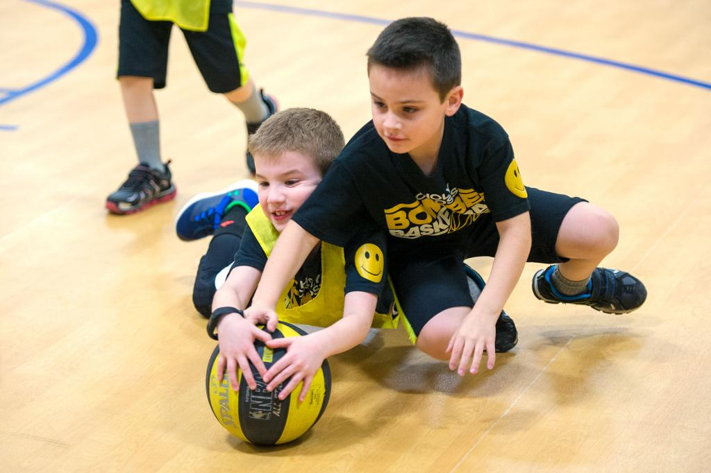 Second-graders Mikey O'Meara (left) and Jack Novick wrestle for the ball during a Jan. 29 CYO basketball game at Holy Cross School.
