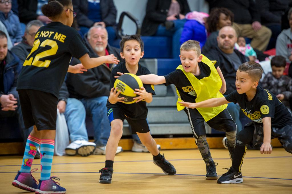 Second-grader Gregorio Vargas (from left) is defended by Jaeden Eldred and Noah Panzardi during a Jan. 29 CYO basketball game at Holy Cross School.