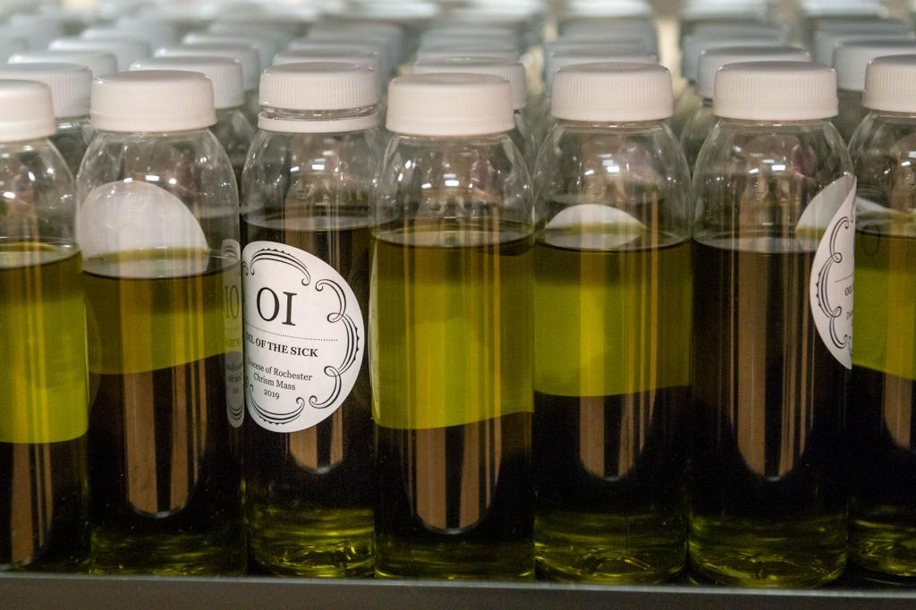 Bottles containing the Oil of the Sick are prepared for distribution to diocesan parishes.