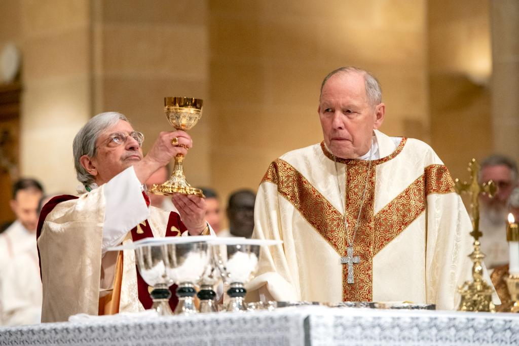 Bishop Emeritus Matthew H. Clark looks on as Bishop Matano elevates the chalice during the consecration.