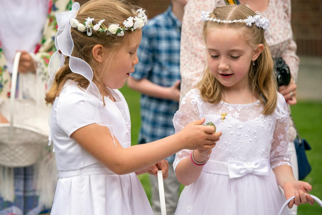 Maja Gan (left) and Emily Whitehouse (right) drop flower petals during the eucharistic procession.