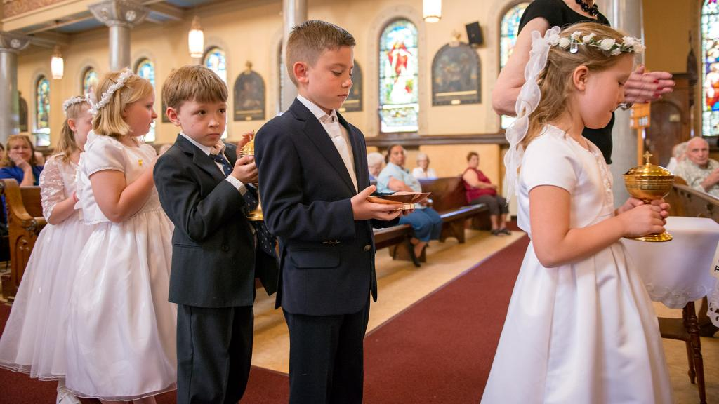 Children who recently made their first Communion -- Emily Whitehouse (from left,) Julia Wnuk, Gabriel Wyrozebski, Adam Mrozek and Maja Gan -- bring forward the gifts during Mass.