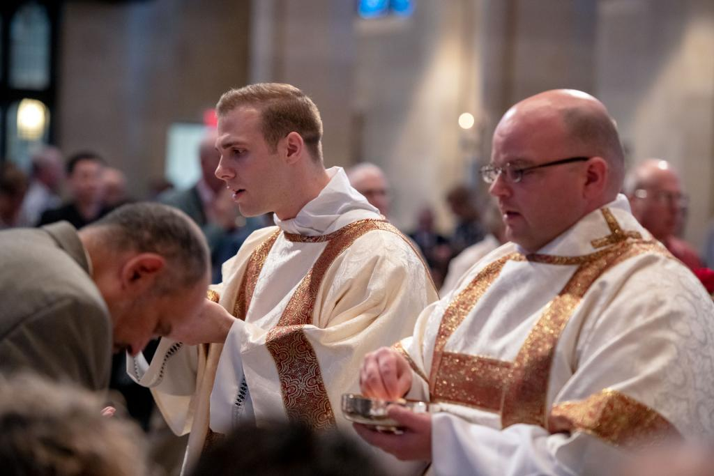 Deacons Joseph Martuscello and Jonathan Schott help to distribute Holy Communion.