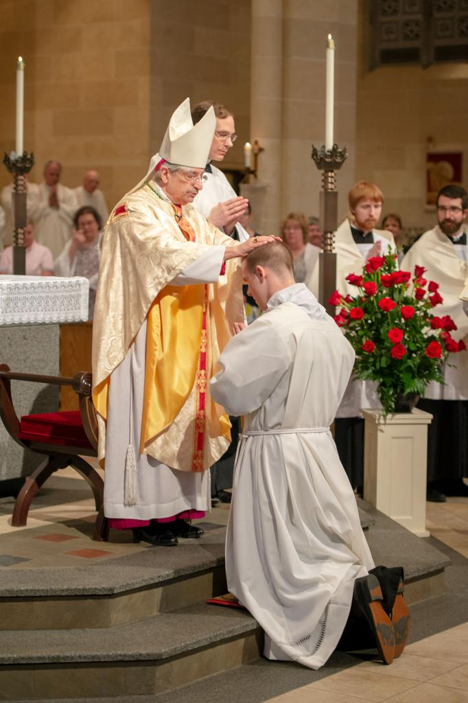 Bishop Matano lays his hands on the head of Joseph Martuscello