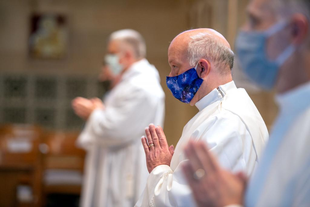 Roger Loucks stands after processing into Rochester's Sacred Heart Cathedral Aug. 15 for the deacon ordination Mass.