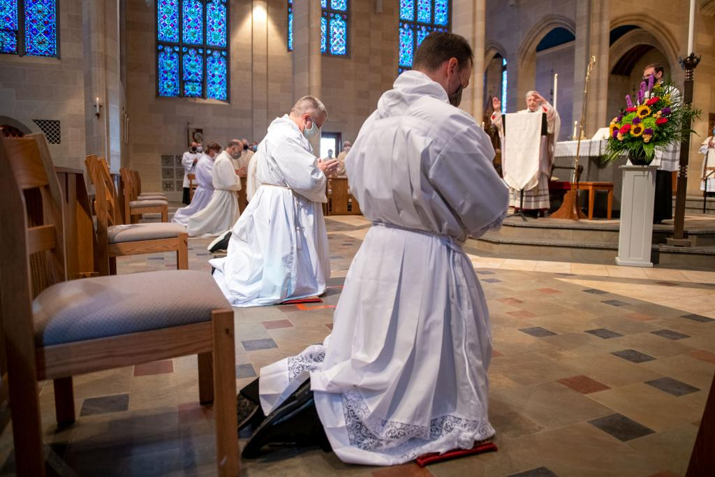 The newly ordained deacons kneel in prayer before Bishop Matano.