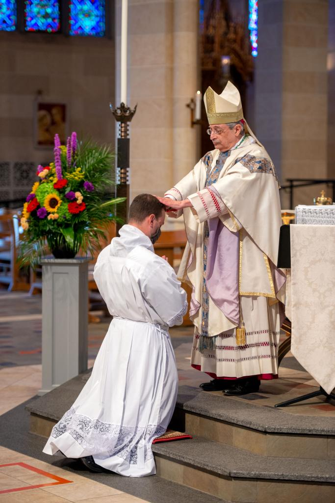 Bishop Matano places his hands on the head of Joseph Maurici.
