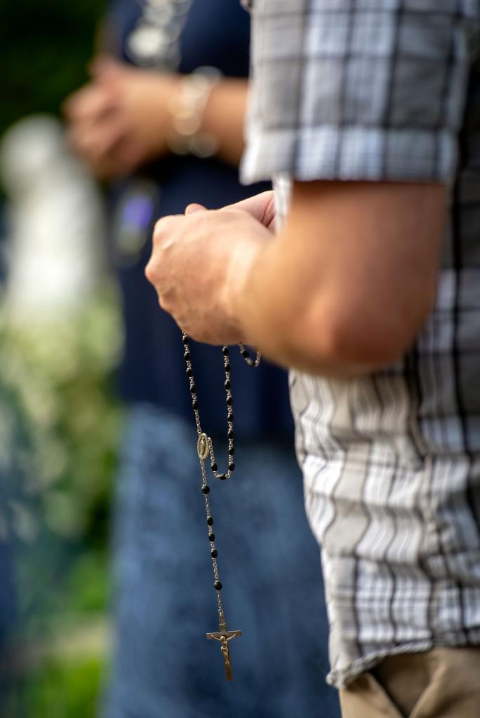 A young adult prays the rosary.