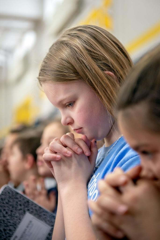Emma Kingsley bows her head in prayer following the pep rally at Holy Cross School in Rochester Jan. 28.