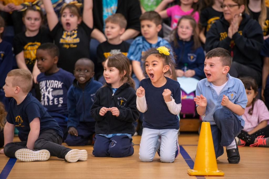 Holy Cross School students cheer during a pep rally and game between sixth-graders and faculty Jan. 28.