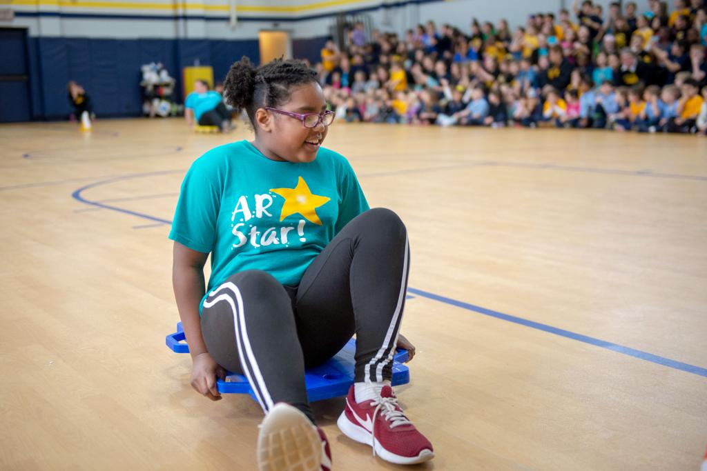 Naomi Whitfield competes in the scooter relay race during Holy Cross School's pep rally Jan. 28.