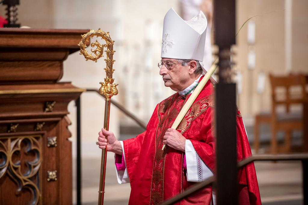 Bishop Salvatore R. Matano carries palms as he processes into an April 5 Palm Sunday Mass to begin Holy Week.