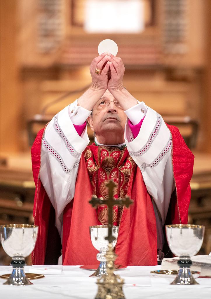 Bishop Matano elevates the Eucharist during the Palm Sunday Mass.