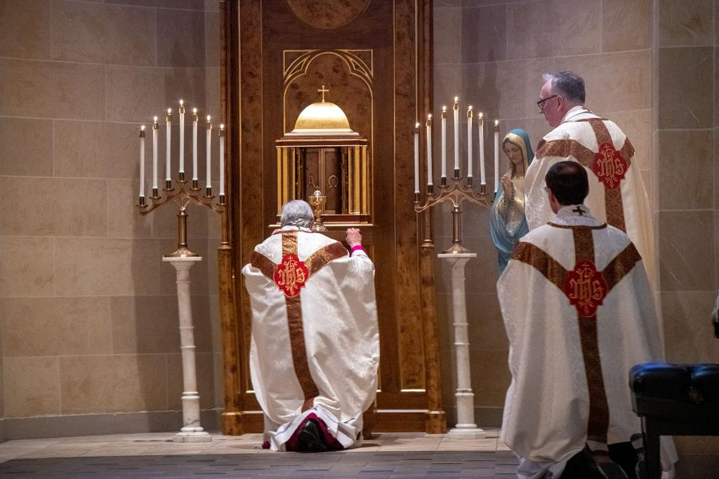 Bishop Matano kneels before the tabernacle following the Holy Thursday Mass April 9.